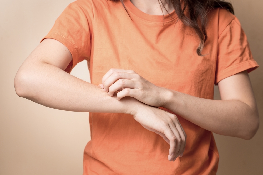 Woman scratching her arms.