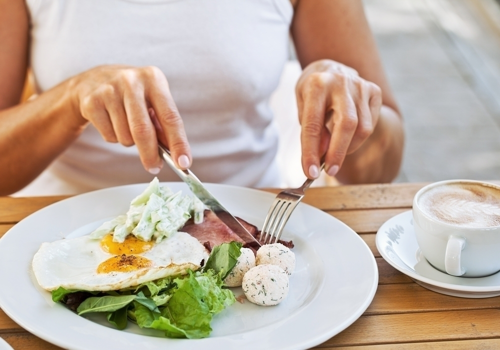 Woman having eggs and bacon.