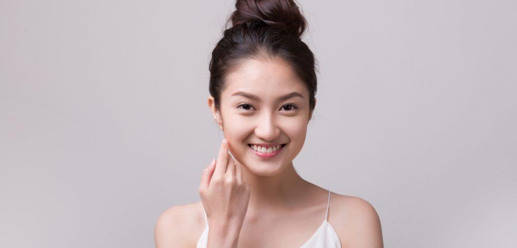 Asian woman touching her face