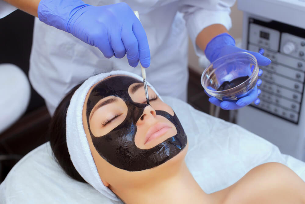 Spa professional applying black face mask on woman's face
