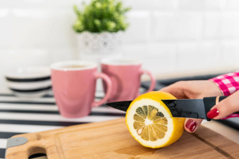 Slicing a lemon on chopping board