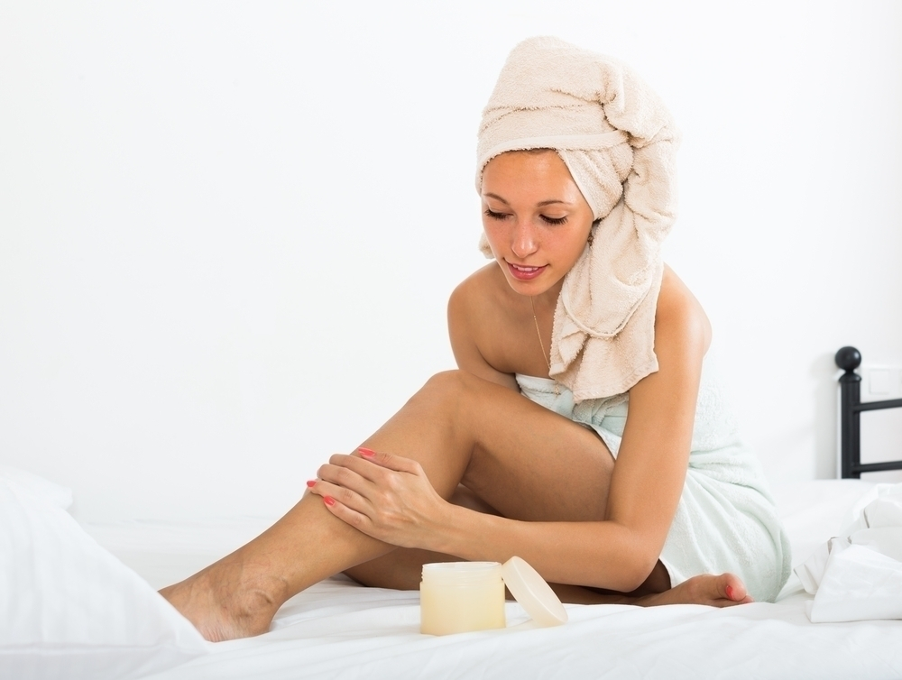 Woman moisturizing feet