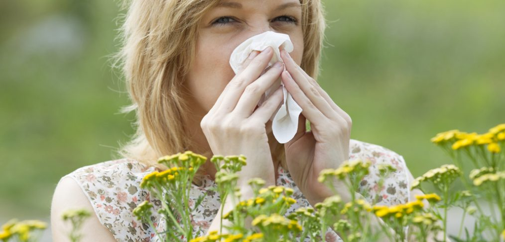 Woman sneezing into napkin outside