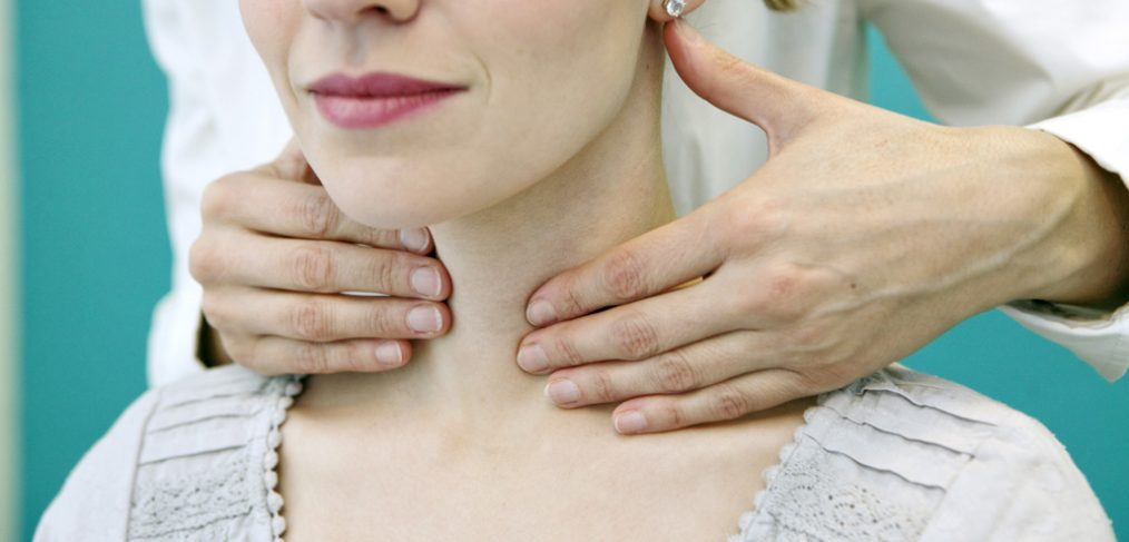 doctor checking a patient for thyroids