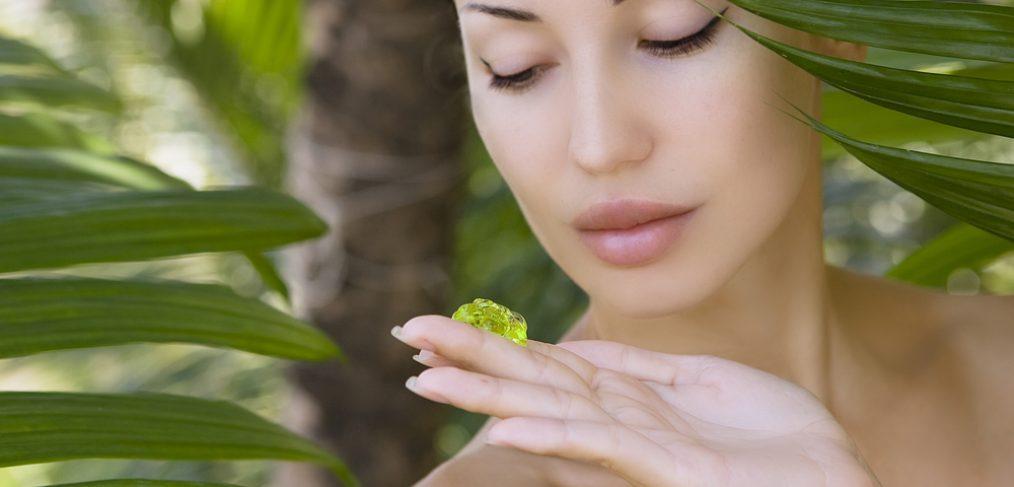 Woman using aloe vera to sooth sunburn