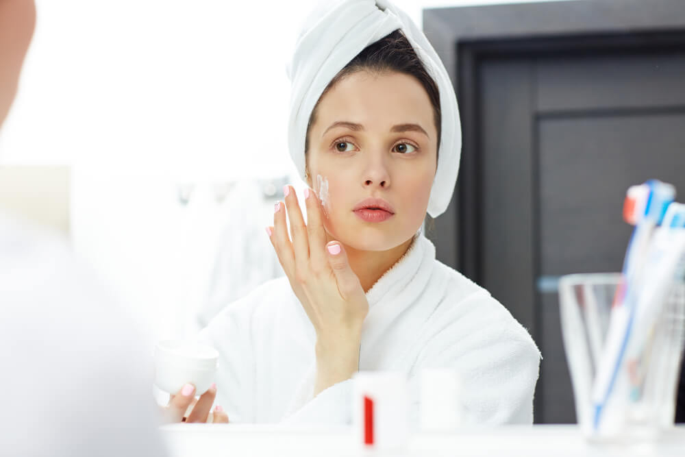 Young woman applying moisturiser to face