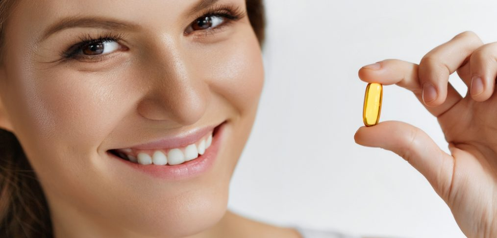 Woman with vitamin D capsule