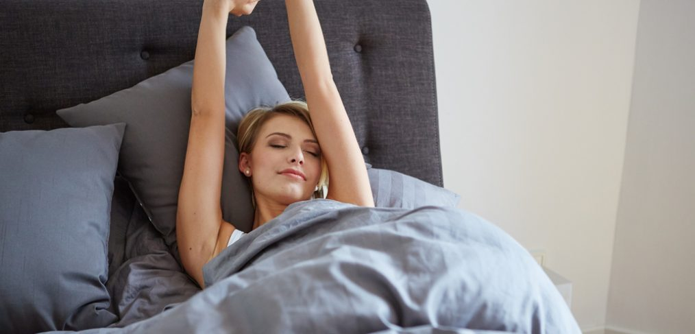 Woman stretching hands after waking up