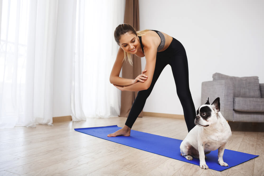 Woman doing yoga at home with her dog
