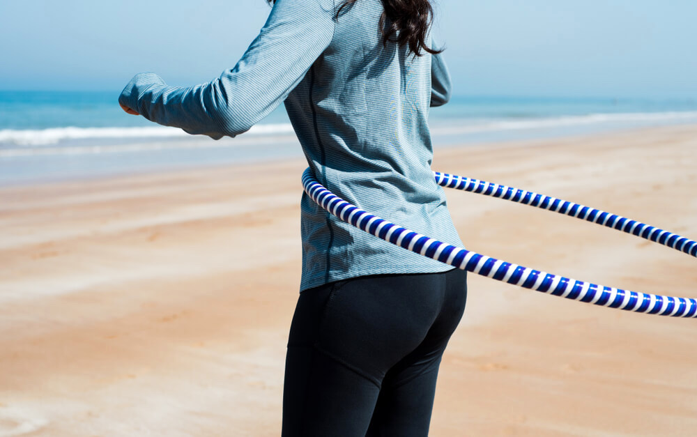 Unknown woman hoola-hooping at the beach