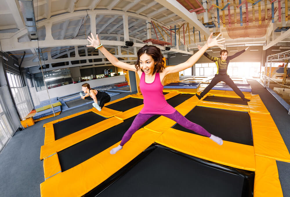 Happy excited woman jumping on large trampoline