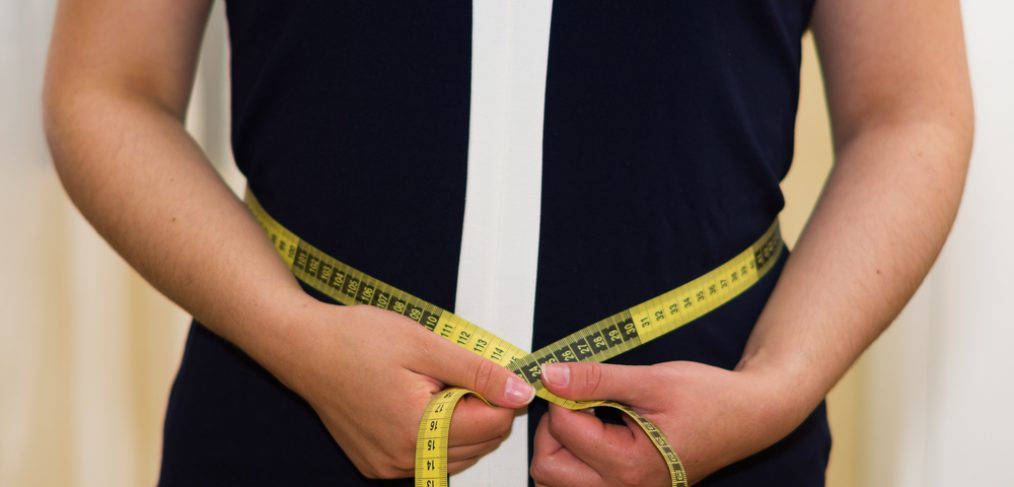 Woman measuring her dress size