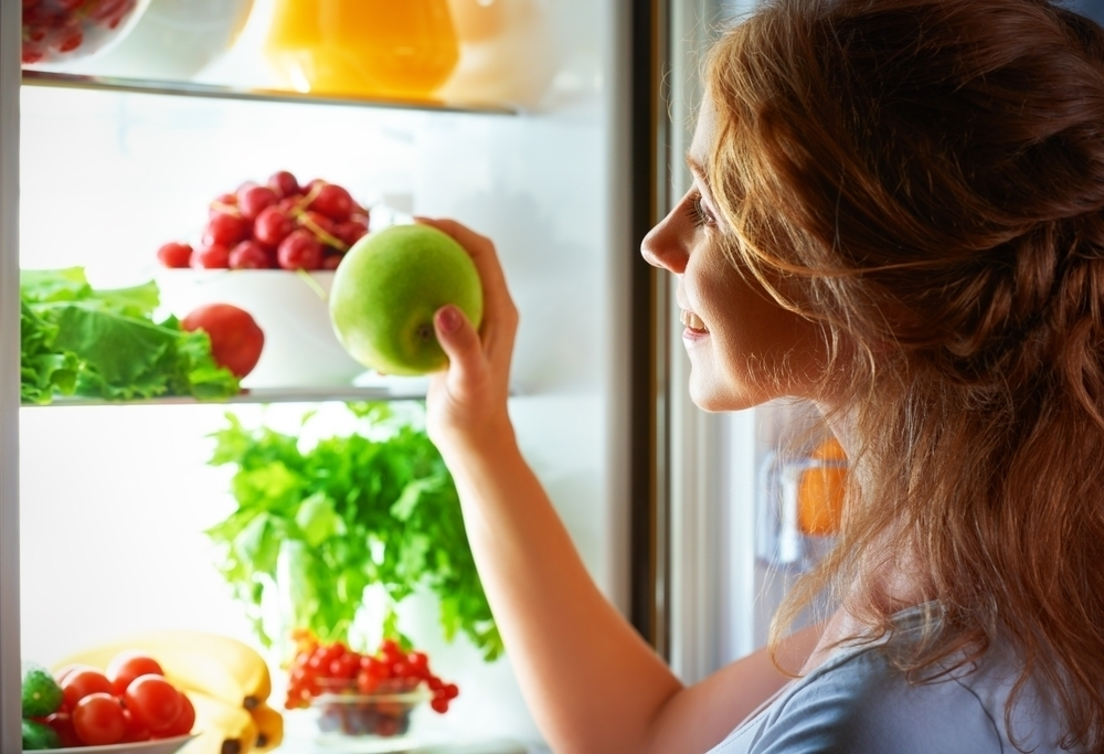 woman eating fruits at night from fridge