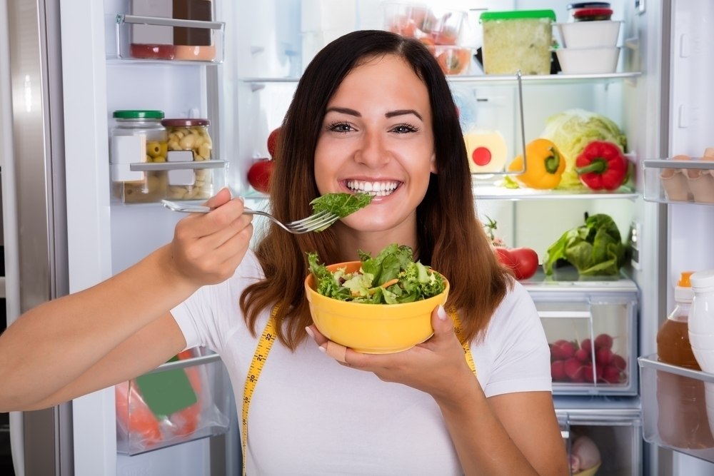 woman eating healthy food from fridge