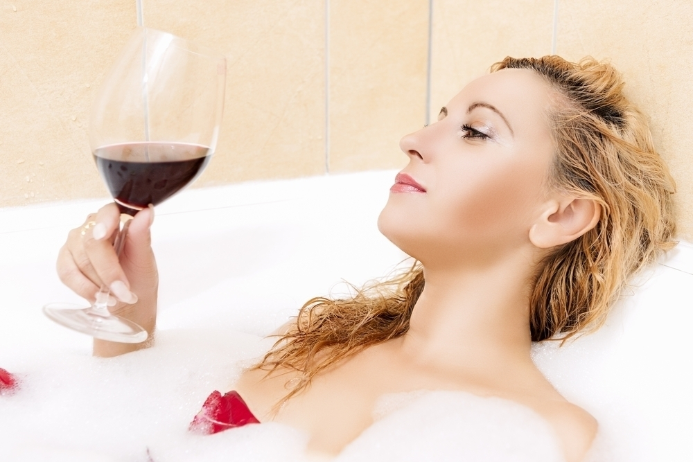 Woman with red wine in bath