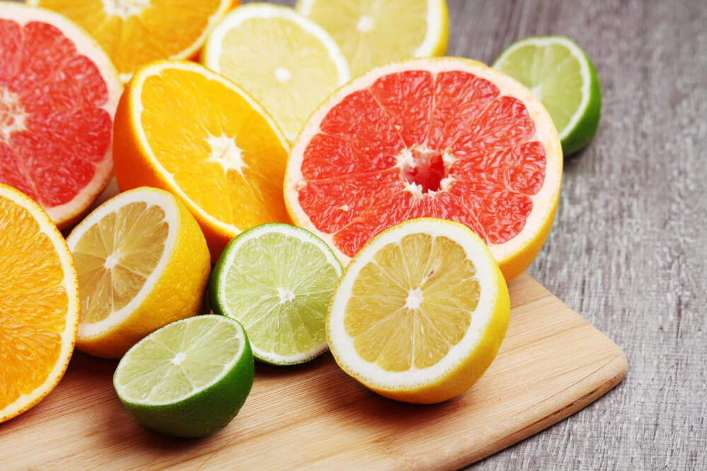 Halved citrus fruits on wooden board
