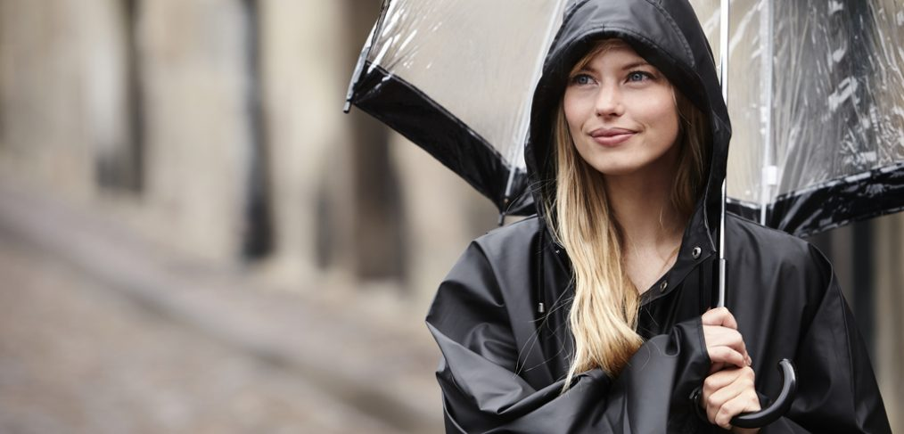 Woman shielding herself from the rain with umbrella