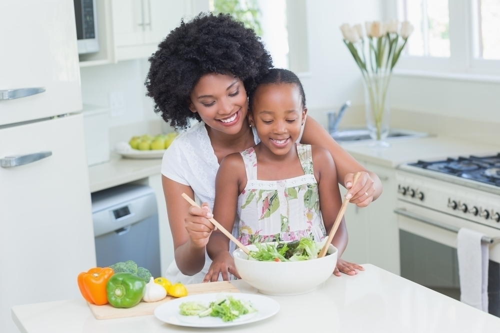 Mother and daughter making salad