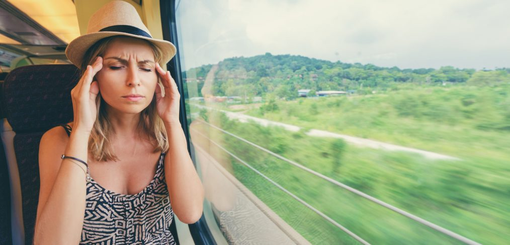Woman holding her head in the train