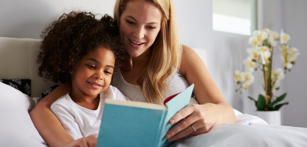 Woman reading bedtime story to child in bed