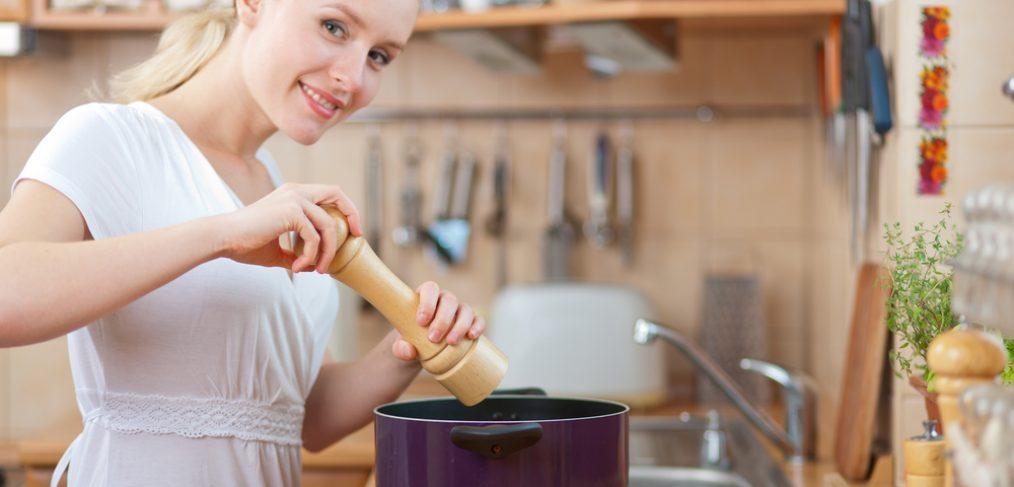 Woman adding salt to cooking