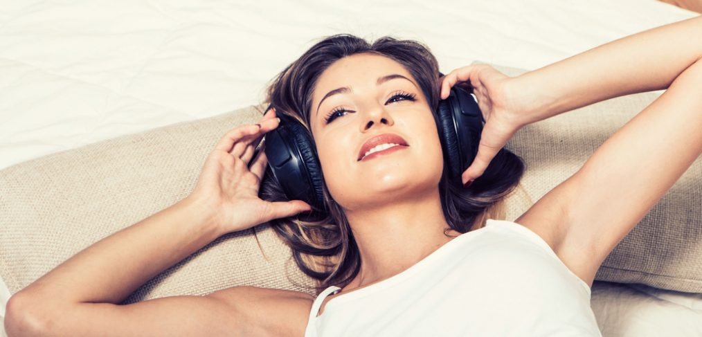 Woman with headphones on the bed