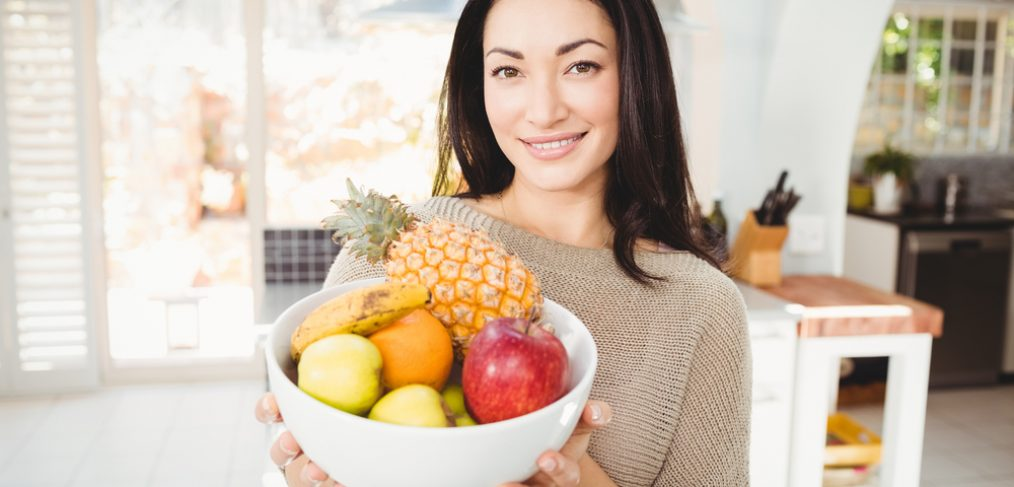 Woman holding a basket of fresh fruits
