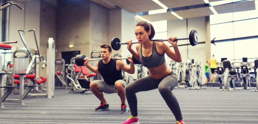 Couple lifting weights in the gym