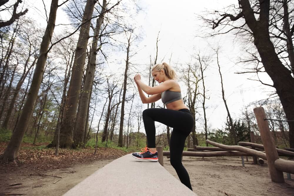 woman doing step-ups outdoors