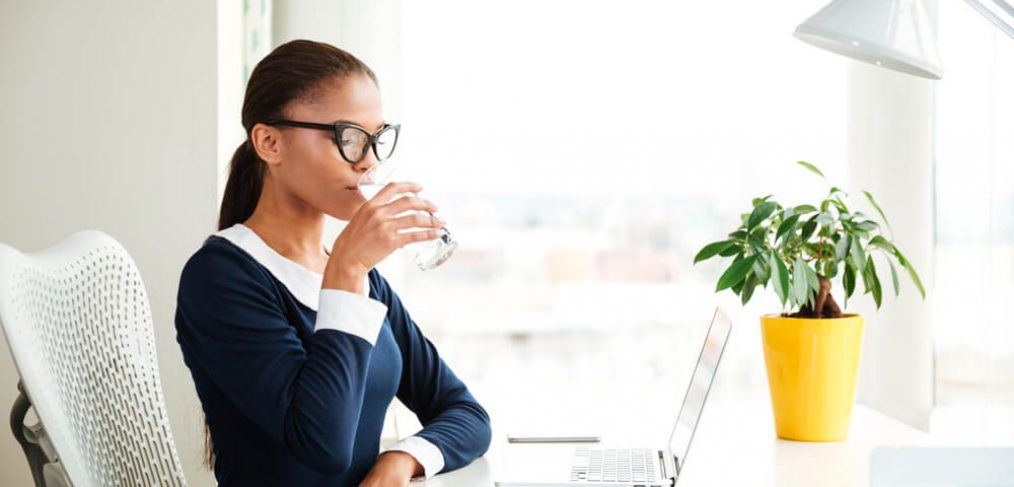 Woman drinking water at her work desk
