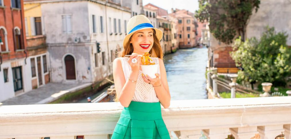 Young woman enjoying spaghetti in Italy