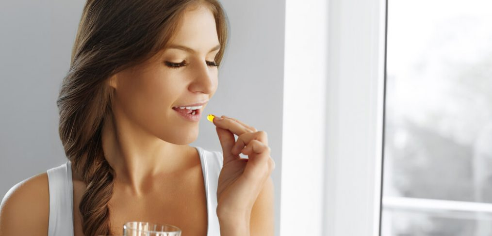 Woman about to take omega-3 pill