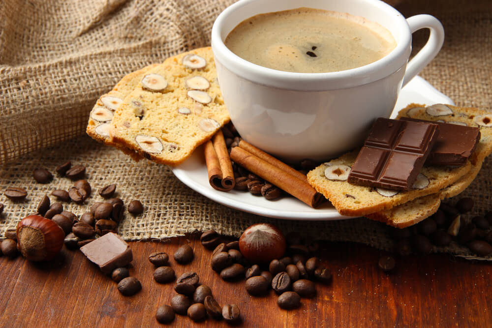 Small cup of espresso, surrounded by biscotti, cinnamon sticks, and coffee beans