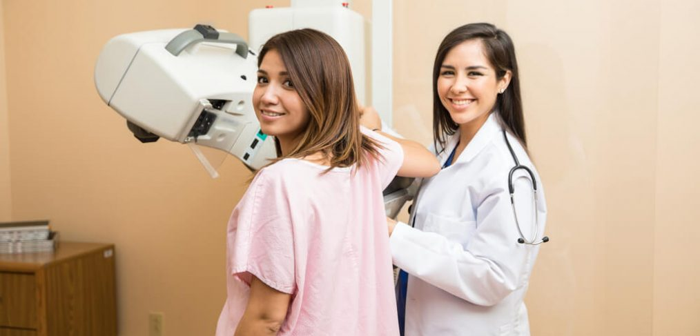 Smiling woman undergoing mammography