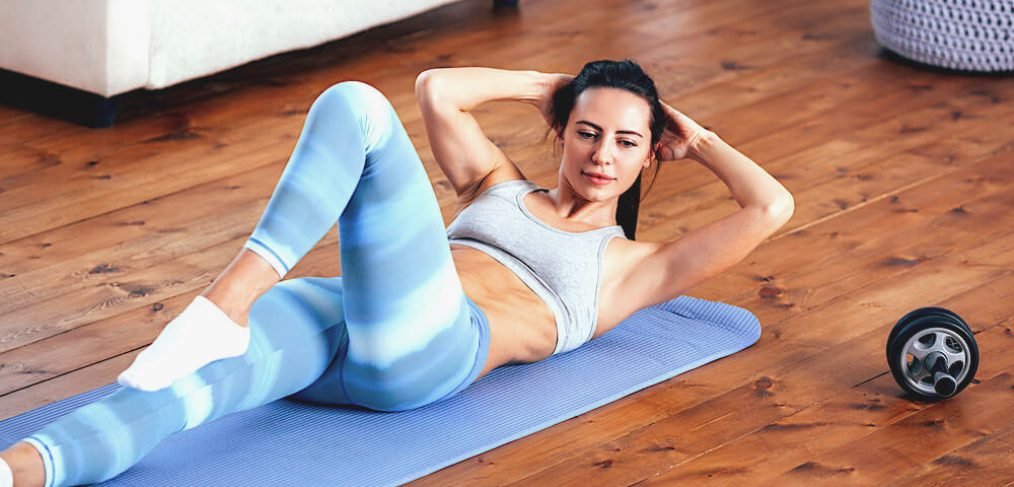 Woman doing crunches on blue exercise mat