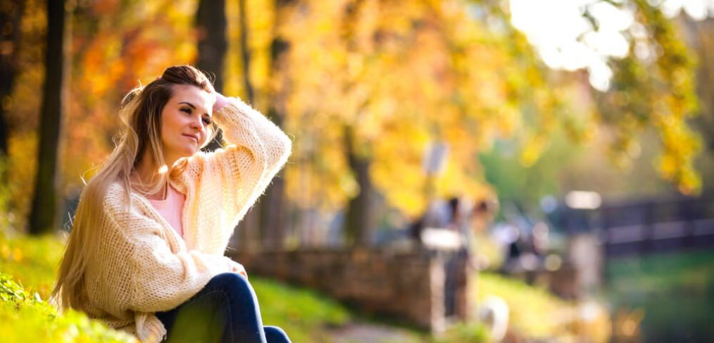 Relaxed woman sitting on the bank of river