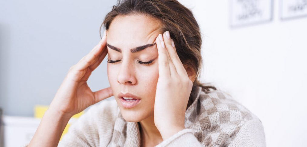 Woman massaging her temples due to a headache