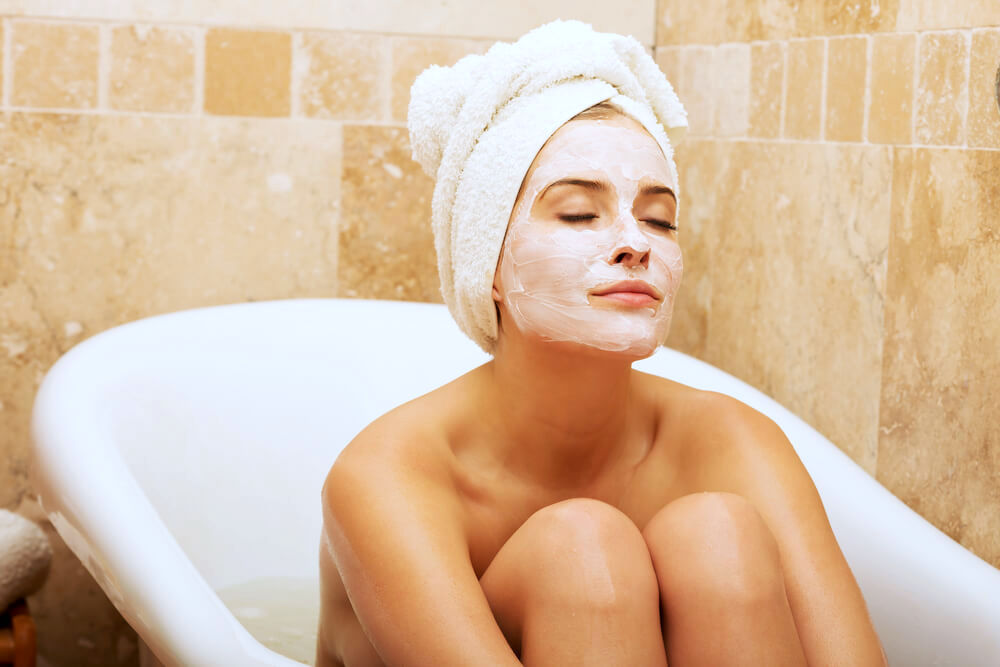 woman relaxing in bath with a face mask