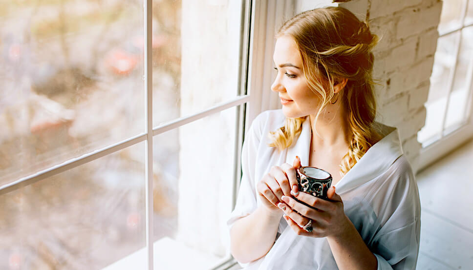 woman drinking tea next to window
