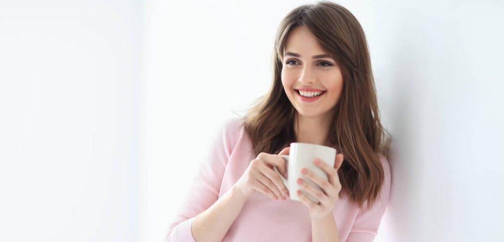 Smiling woman nursing a cup of tea