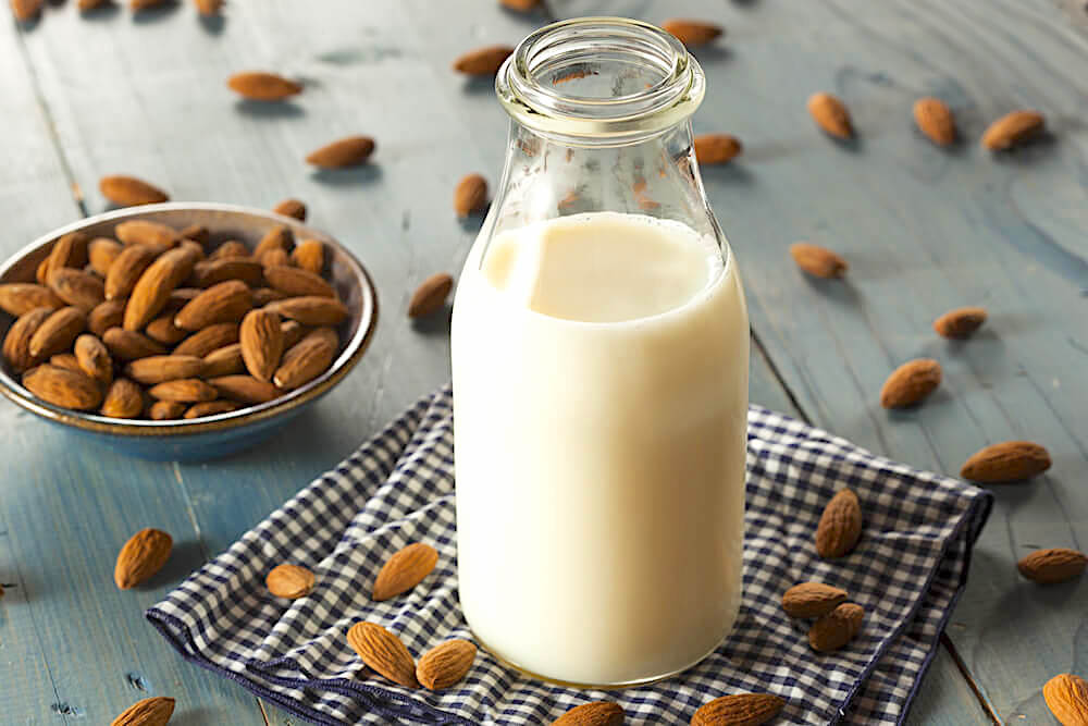 Jar of fresh almond milk, surrounded by loose almonds