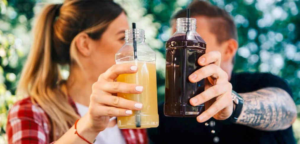 Couple holding up bottled juices