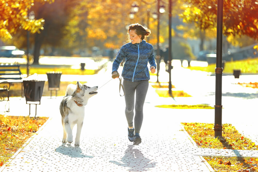 woman running outside with dog