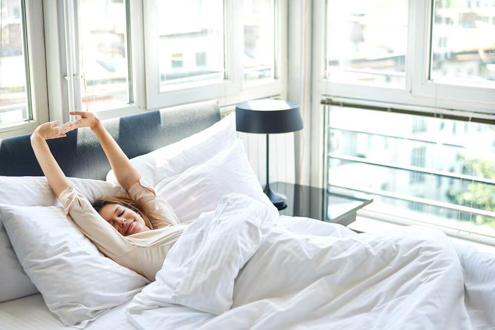 Woman stretching in bed, waking up