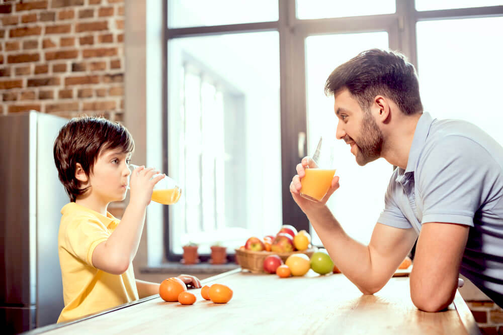 Father and son drinking orange juice in the kitchen