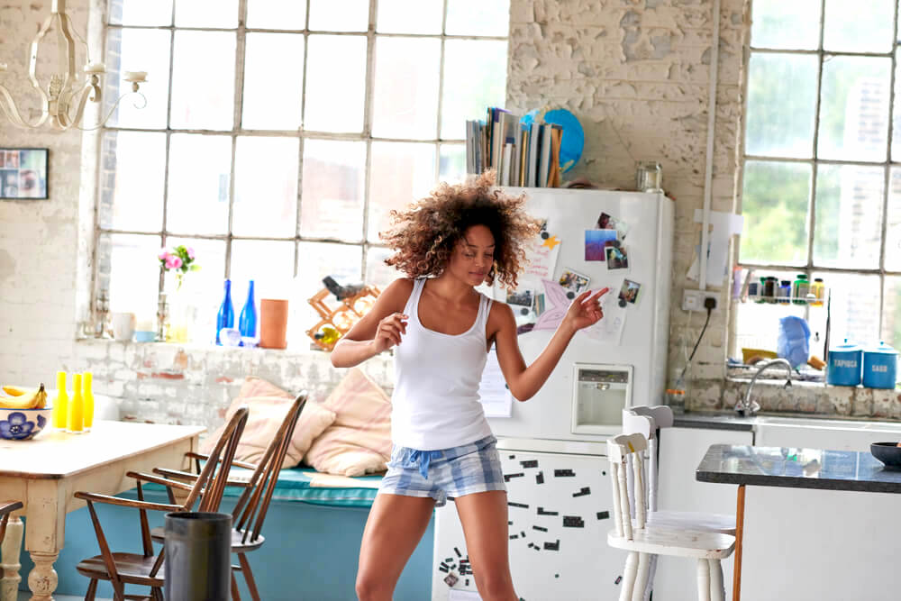 Young woman dancing in the kitchen