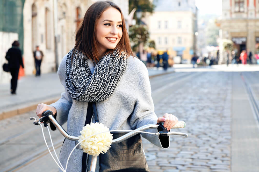 Happy young woman cycling in the city