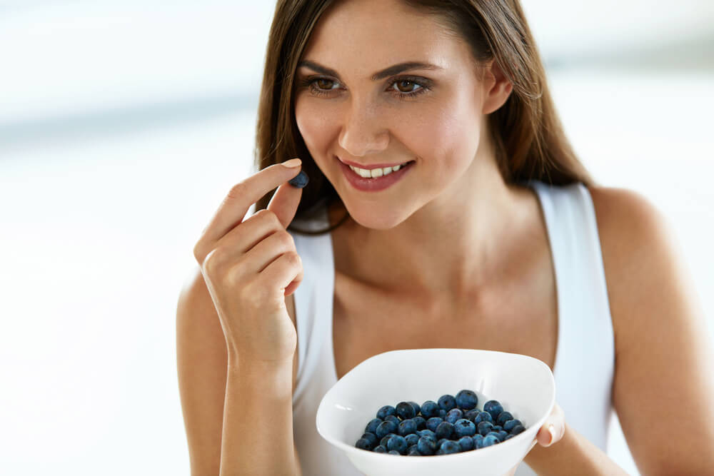 Woman enjoying blueberries in a bowl