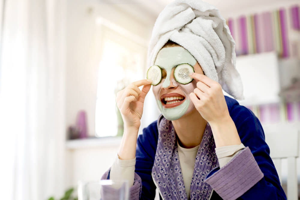 Applying face mask with cucumber slices