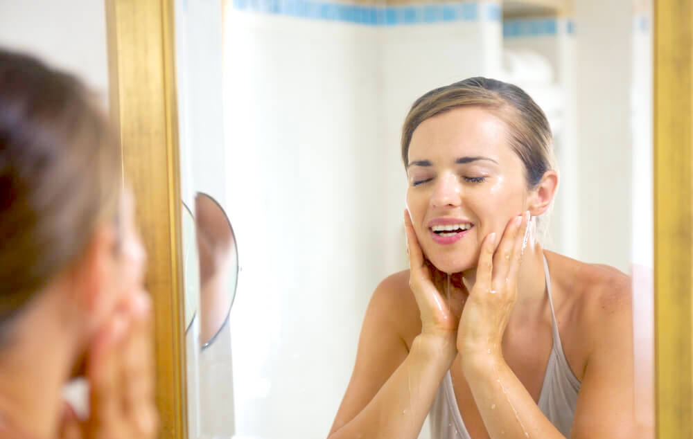 Attractive woman washing face in mirror